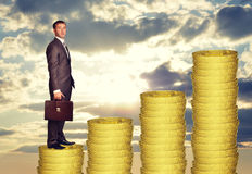 Businessman standing on coins steps Stock Photos