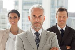 Businessman standing with colleagues behind Stock Photography