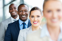 Businessman standing colleagues. Happy african american businessman standing in a row with colleagues royalty free stock images