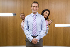 Businessman standing with colleagues in line behind, peeking out, smiling, portrait Royalty Free Stock Photography