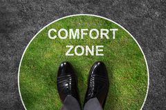 Businessman Standing In Comfort Zone Text. Businessman standing on green and gray carpet with comfort zone text on it royalty free stock photos