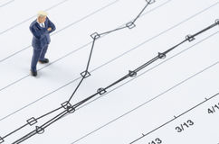 Businessman standing on the compare graph. Miniature businessman standing on the compare graph stock photos