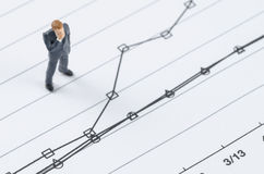 Businessman standing on the compare graph. Miniature businessman standing on the compare graph stock photography