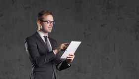 Businessman standing with computer tablet on a dark background. Stock Photos