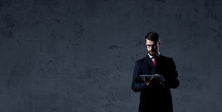 Businessman standing with computer tablet over dark wall backgro Royalty Free Stock Images