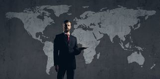 Businessman standing with computer tablet. World map background. Business, globalization, concept Royalty Free Stock Photography