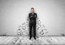 Businessman standing on concrete wall with business sketches passing to the floor. Front view. Stock Photo