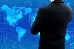 Businessman standing and cross one's arm watching world map Royalty Free Stock Image