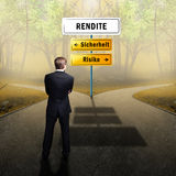 Businessman standing on a crossroad, having to choose the right path to yield with the words yield, safety and risk Royalty Free Stock Image