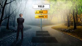 Businessman standing at a crossroad of Yield royalty free stock photos