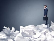 Businessman standing on crumpled paper Stock Photos