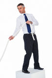 Businessman standing on a cube and pulling rope. On white background Royalty Free Stock Photo