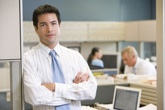 Businessman standing in cubicle. Looking at camera Stock Photo