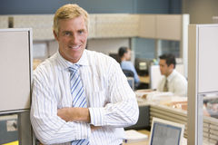Businessman standing in cubicle smiling. At camera Royalty Free Stock Photos
