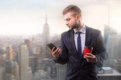 Businessman standing with a cup of coffee and a phone. In his hand Royalty Free Stock Photos