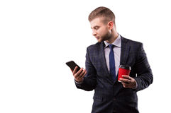 Businessman standing with a cup of coffee and a phone. In his hand Stock Photography