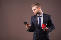 Businessman standing with a cup of coffee and a phone. In his hand Royalty Free Stock Image