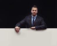 Businessman standing on dark background Stock Photos