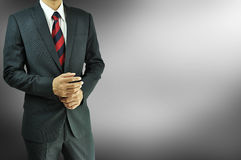 Businessman standing in dark gray background Stock Photography