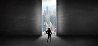 Businessman looking to a cityscape from a dark empty room royalty free stock photography