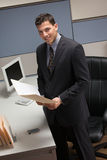 Businessman standing at desk in cubicle. Young businessman standing at desk in cubicle holding file folder Royalty Free Stock Image