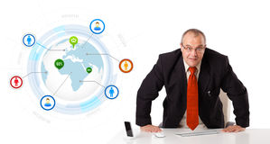 Businessman standing at desk with globe and social icons Royalty Free Stock Image
