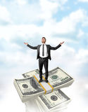 Businessman standing on the dollar stack top with a crossed bundle of money Royalty Free Stock Image