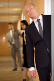 Businessman standing at door while colleagues in background Royalty Free Stock Photos