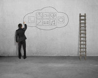 Businessman standing and drawing app icon on concrete wall Royalty Free Stock Photography