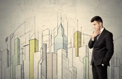 Businessman standing with drawn cityscape. A young adult businessman standing in front of a wall with colorful drawings of buildings, charts, graphs, signs Royalty Free Stock Photos