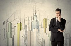 Businessman standing with drawn cityscape Royalty Free Stock Photos