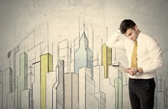 Businessman standing with drawn cityscape Stock Photography