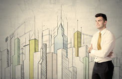 Businessman standing with drawn cityscape Stock Image