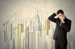 Businessman standing with drawn cityscape. A young adult businessman standing in front of a wall with colorful drawings of buildings, charts, graphs, signs Royalty Free Stock Photography
