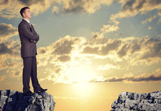 Businessman standing on the edge of rock gap Stock Image