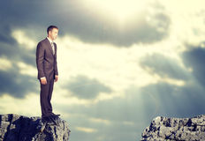 Businessman standing on the edge of rock gap Royalty Free Stock Photography