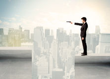 Businessman standing on the edge of rooftop Stock Photo