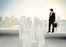 Businessman standing on the edge of rooftop Royalty Free Stock Images