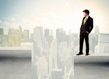 Businessman standing on the edge of rooftop Royalty Free Stock Image