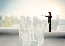 Businessman standing on the edge of rooftop Stock Photos