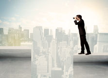 Businessman standing on the edge of rooftop Stock Images