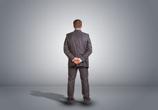 Businessman standing in an empty gray room. Rear Stock Photos