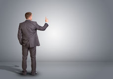 Businessman standing in an empty gray room. Rear Royalty Free Stock Photo