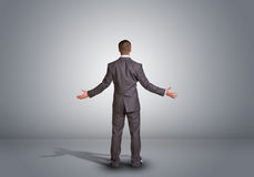 Businessman standing in an empty gray room. Rear Royalty Free Stock Photography