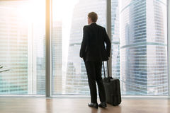 Businessman standing in the empty office. Young businessman with suitcase standing looking at full length window, dreaming to move only forward, high rental royalty free stock image