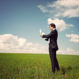 Businessman standing on a field with a blue sky and reads the ne Royalty Free Stock Photo