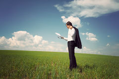 Businessman standing on a field with a blue sky and reads the ne Stock Photos
