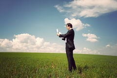 Businessman standing on a field with a blue sky and reads the ne Stock Image