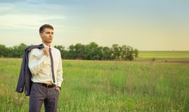 Businessman standing in field and looking forward. Businessman standing in field , looking forward and thinking Royalty Free Stock Photography