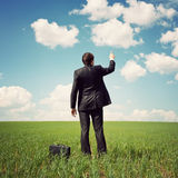 Businessman standing in the field and points a finger Royalty Free Stock Photos